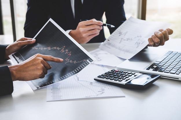 Gruppo di affari che lavora con il mercato azionario del grafico del computer, del computer portatile, di discussione e dell'analisi