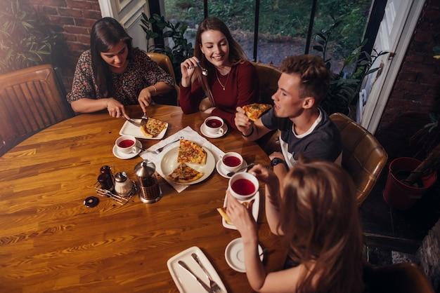 Gruppo di amici a cena a tavola rotonda a parlare e sorridere