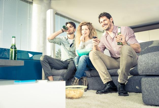 Gruppo di amici a guardare la televisione in salotto