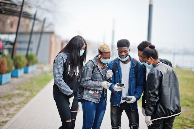 Gruppo di amici adolescenti africani al parco che indossano maschere mediche proteggono da infezioni e malattie quarantena del virus coronavirus, leggi notizie scioccate sul telefono.