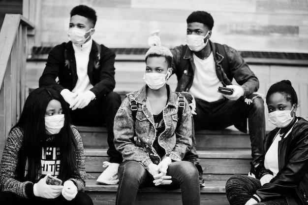 Gruppo di amici adolescenti africani al parco che indossano maschere mediche proteggono da infezioni e malattie quarantena del virus coronavirus.