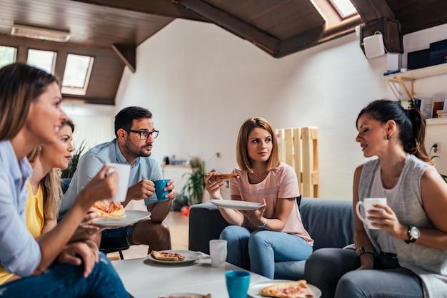 Gruppo di amici adulti parlando e mangiando pizza a casa.