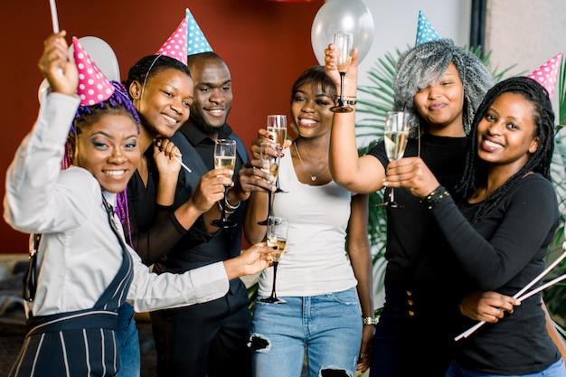 Gruppo di amici africani felici che bevono champagne e che celebrano il nuovo anno. festa di fine anno. festa di compleanno