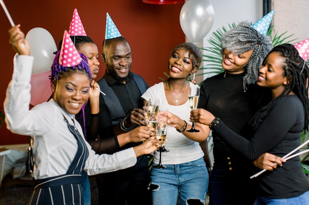 Gruppo di amici africani felici che bevono champagne e che celebrano la festa di compleanno