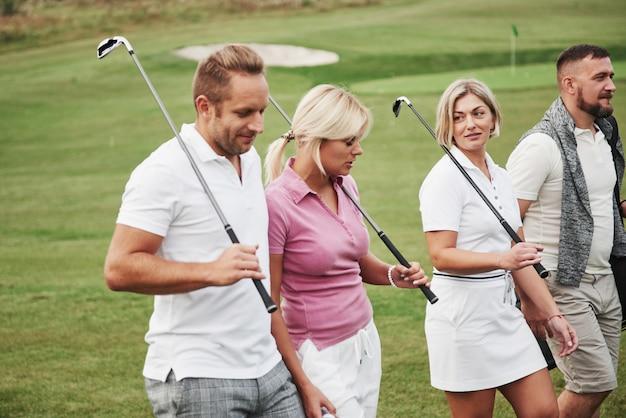 Gruppo di amici alla moda sul campo da golf imparano a giocare a un nuovo gioco. la squadra si riposerà dopo la partita