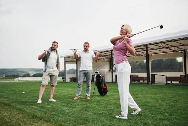 Gruppo di amici alla moda sul campo da golf imparano a giocare a un nuovo gioco