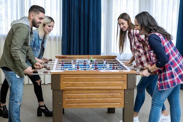 Gruppo di amici allegri che giocano a calcio balilla