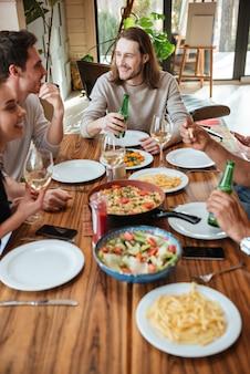 Gruppo di amici allegri che mangiano e che parlano al tavolo