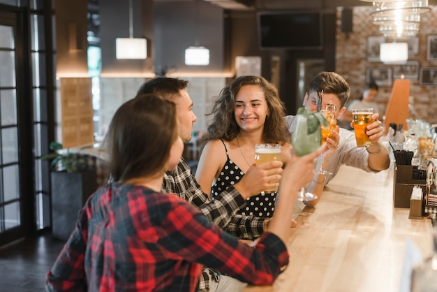 Gruppo di amici allegri godendo drink nel pub