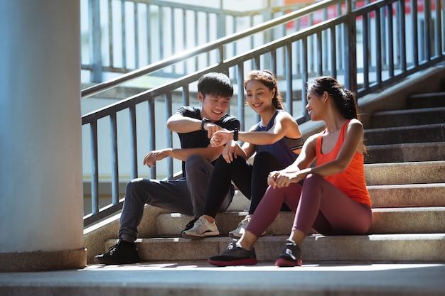 Gruppo di amici asiatici che fanno jogging al mattino, parlano, si siedono e riposano