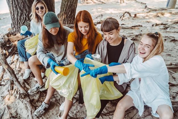 Gruppo di amici attivisti che raccolgono rifiuti di plastica al parco. conservazione dell'ambiente.