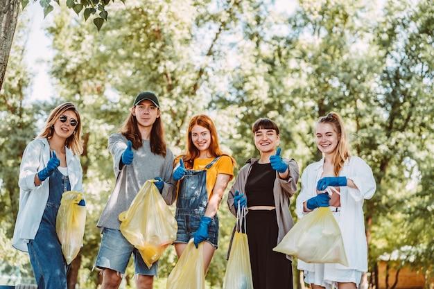 Gruppo di amici attivisti che raccolgono rifiuti di plastica. i ragazzi mostrano il pollice in su.