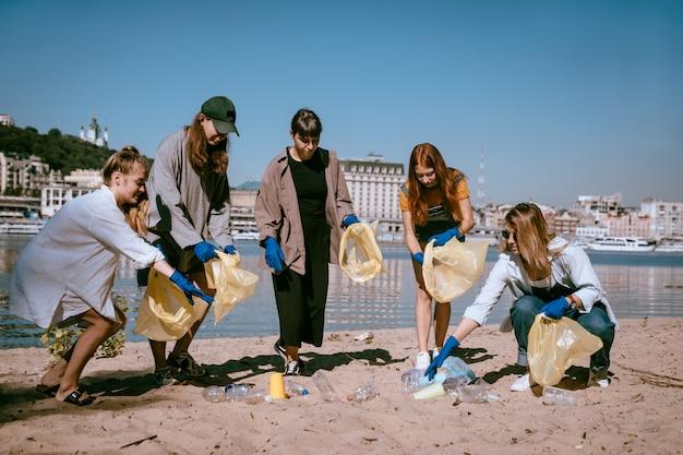 Gruppo di amici attivisti che raccolgono rifiuti di plastica sulla spiaggia. conservazione dell'ambiente.