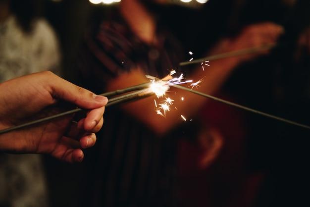Gruppo di amici che accendono insieme le luci del bengala. amicizia.