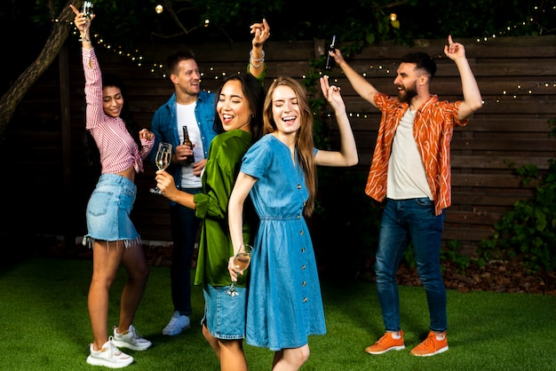 Gruppo di amici che ballano insieme all'aperto