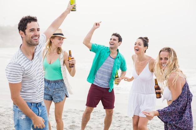 Gruppo di amici che ballano sulla spiaggia con bottiglie di birra