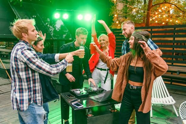 Gruppo di amici che bevono birra, ballano al ritmo della musica, chiacchierano e si divertono alla festa estiva all'aperto.