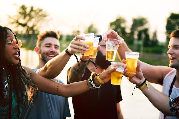 Gruppo di amici che bevono birre godendo insieme il festival di musica