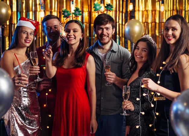 Gruppo di amici che celebrano con fuochi d'artificio e bicchieri godendo la festa di natale