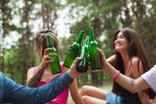 Gruppo di amici che clinking le bottiglie di birra durante il picnic nella foresta di estate