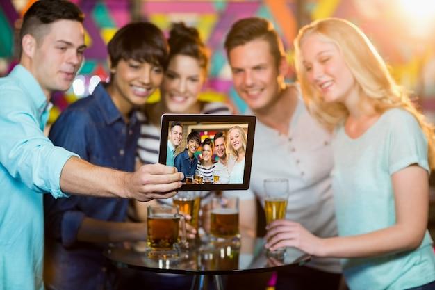 Gruppo di amici che fanno clic su una foto dalla tavoletta digitale