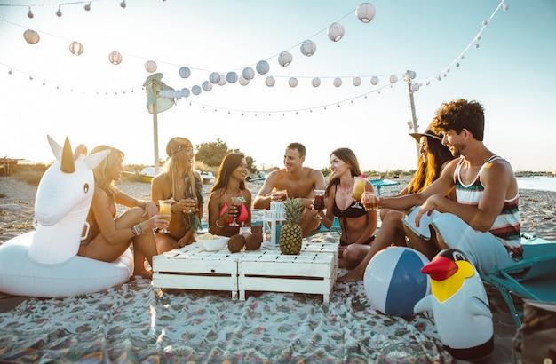 Gruppo di amici che fanno festa sulla spiaggia al momento del tramonto