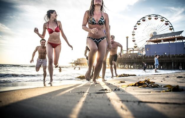 Gruppo di amici che fanno grande festa e giochi sulla spiaggia