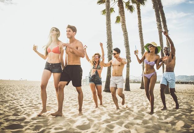 Gruppo di amici che fanno grande festa sulla spiaggia