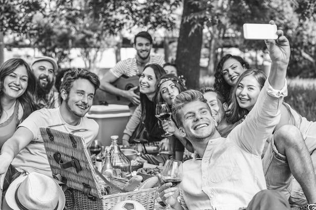 Gruppo di amici che fanno un barbecue di picnic e che prendono selfie con lo smartphone mobile in parco all'aperto