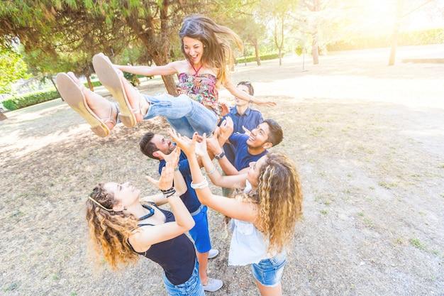 Gruppo di amici che gettano una donna in aria