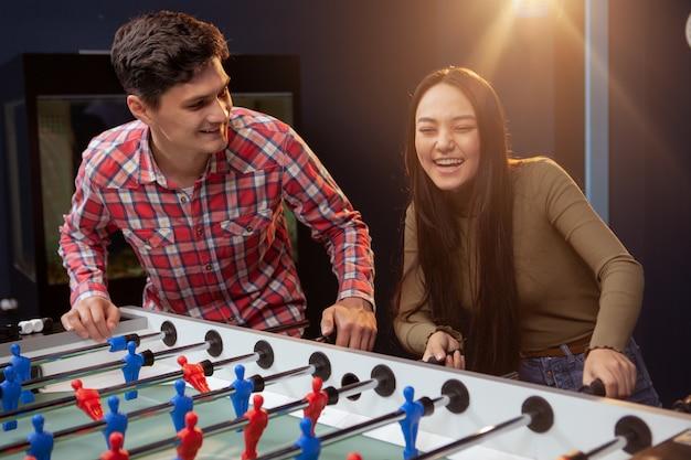 Gruppo di amici che giocano a calcio balilla al pub della birra