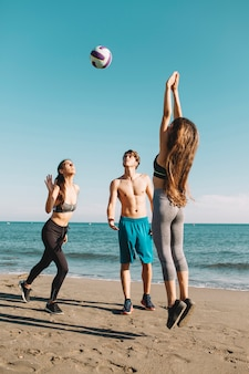 Gruppo di amici che giocano a pallavolo in spiaggia