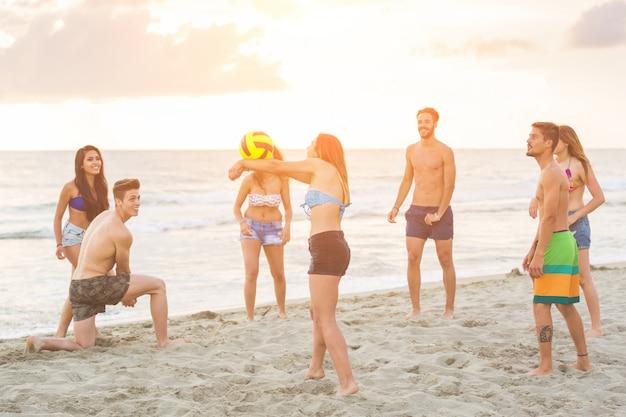 Gruppo di amici che giocano con la palla sulla spiaggia