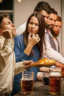 Gruppo di amici che godono della sera bevande con birra