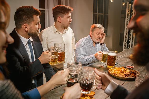 Gruppo di amici che godono di drink serali con birra sulla tavola di legno