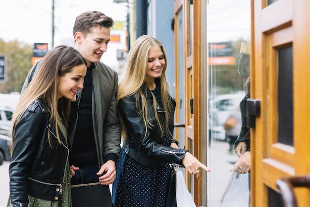 Gruppo di amici che godono lo shopping della finestra