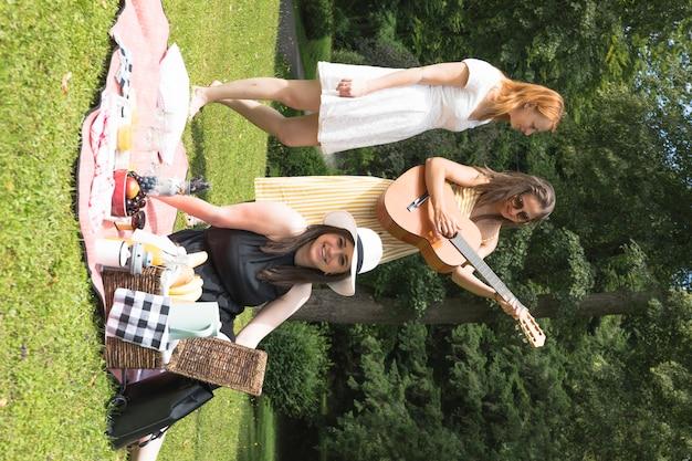 Gruppo di amici che godono sul picnic nel parco