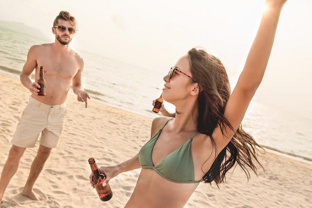 Gruppo di amici che hanno festa in spiaggia in estate