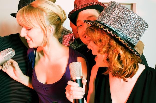 Gruppo di amici che hanno una festa di karaoke