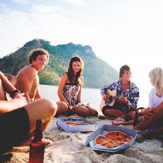 Gruppo di amici che hanno una festa in spiaggia d'estate.