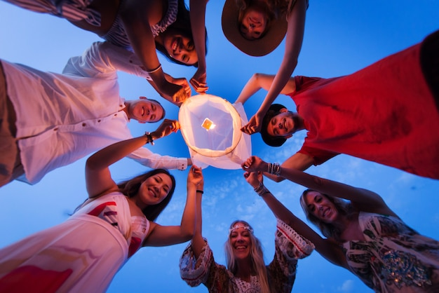 Gruppo di amici che illuminano le lanterne