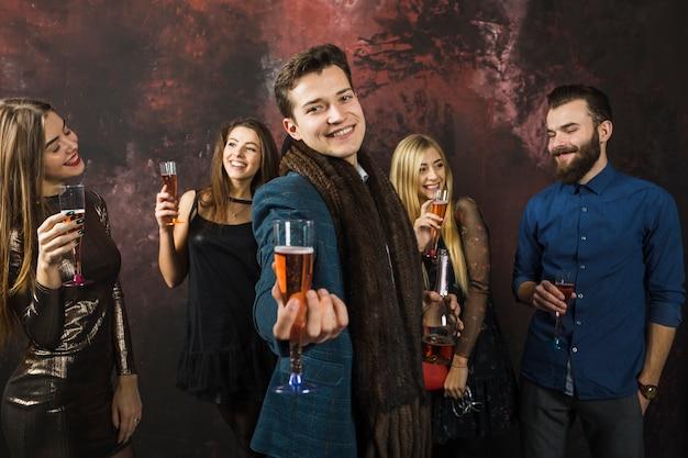 Gruppo di amici che mostrano bicchieri di champagne