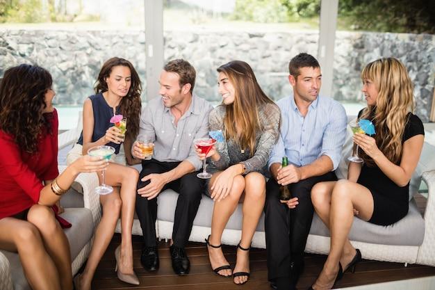 Gruppo di amici che parlano tra loro e cocktail drink alla festa