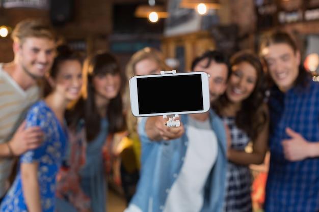 Gruppo di amici che prendono selfie tramite telefono cellulare