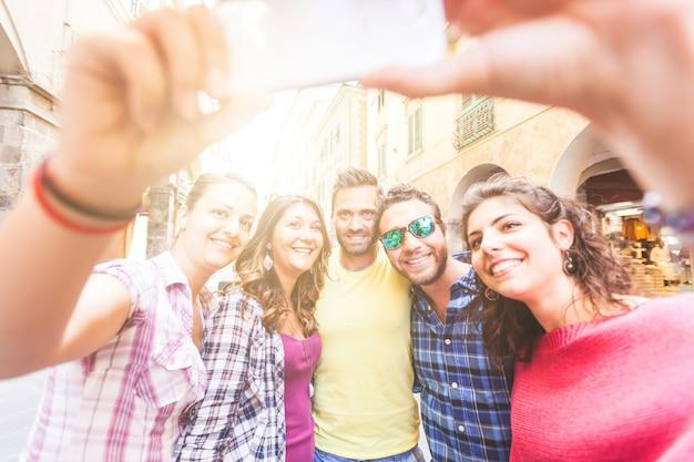 Gruppo di amici che prendono un selfie in città