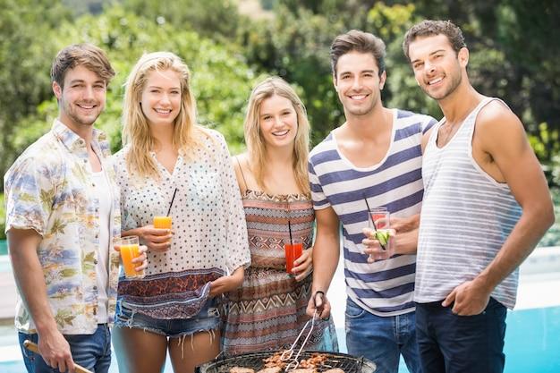 Gruppo di amici che preparano barbecue vicino allo stagno