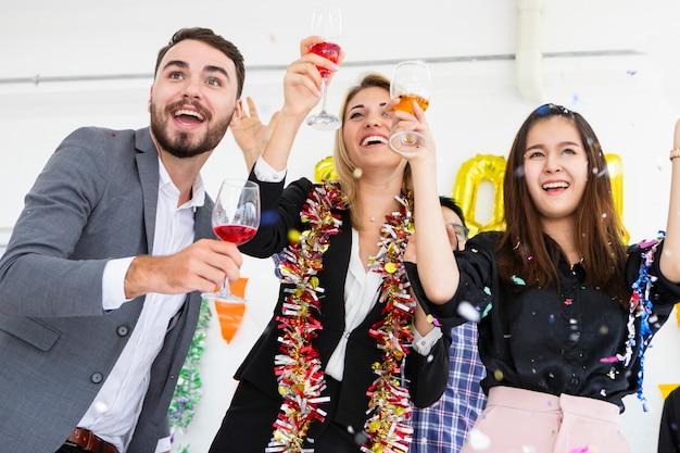 Gruppo di amici che ridono celebrando tenendo flauti di champagne mentre ballano alla festa sulla stanza bianca.