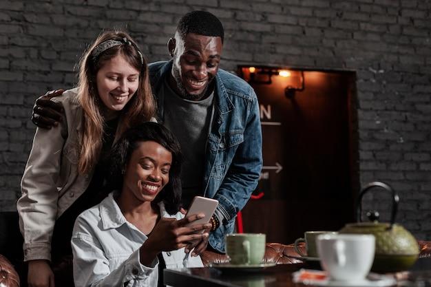 Gruppo di amici che ridono del telefono