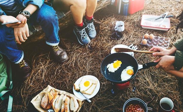Gruppo di amici che si accampano insieme cucinando cibo