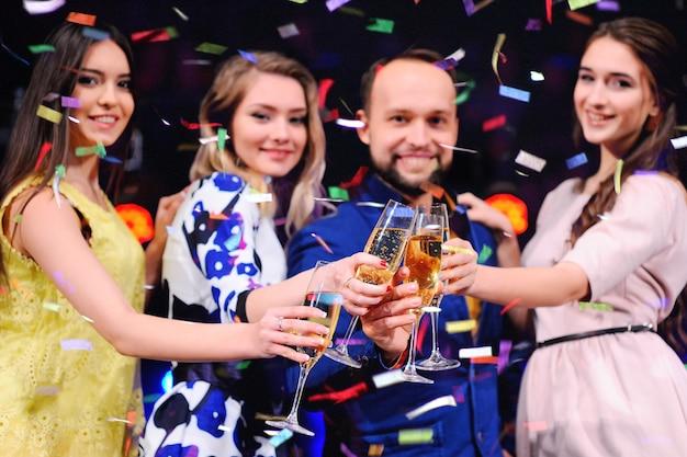 Gruppo di amici che si diverte alla festa con un bicchiere di vino o champagne